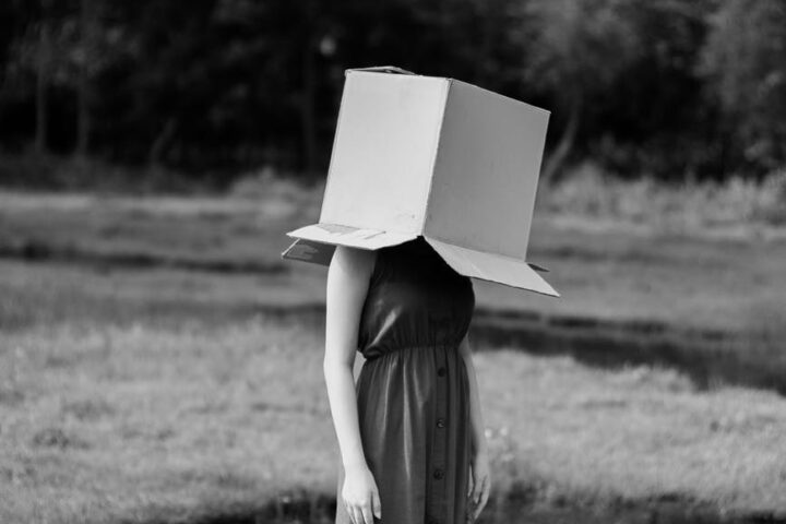 faceless woman with cardboard box on head against pond