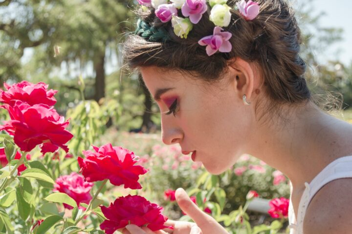 woman in floral headdress sniffing on red flowers